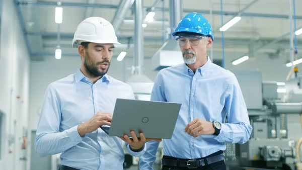 Head of the project holds laptop and discusses product details with chief engineer while they walk through modern factory Royalty-free stock video