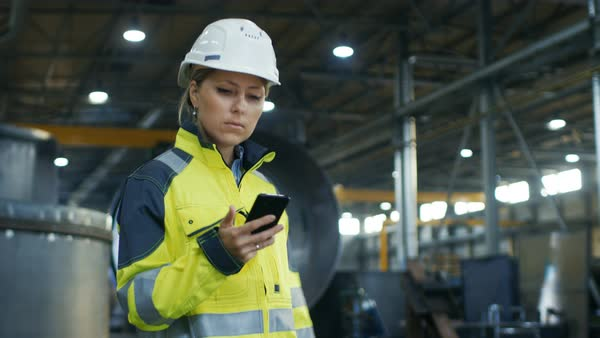 Female industrial worker in the hard hat uses mobile phone while walking through heavy industry manufacturing factory Royalty-free stock video