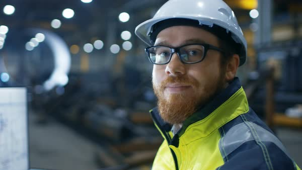 Industrial engineer wearing hard hat, safety jacket and glasses smiles at camera in big heavy industry factory Royalty-free stock video