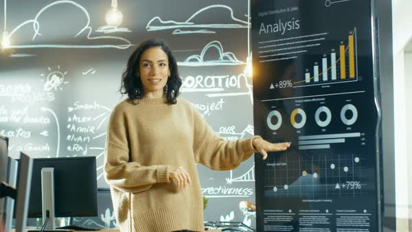Female project manager holds meeting shows statistical graphs and charts on the interactive whiteboard touchscreen device. She works in the stylish creative agency.  Royalty-free stock video