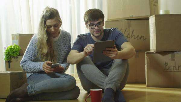 Young couple is using phone and tablet for entertainment in new house Royalty-free stock video