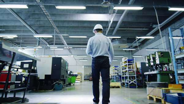Engineer in hard hat is walking through factory. back view Royalty-free stock video