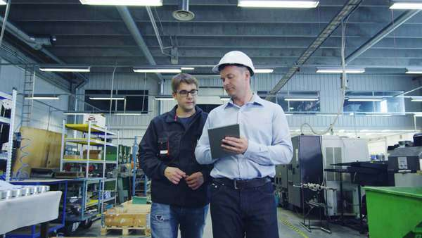 Engineer in hard hat and factory worker are walking through production facility Royalty-free stock video