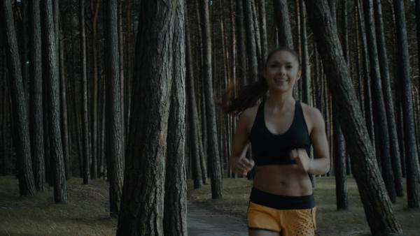 Young girl is running in forest at early morning time Royalty-free stock video