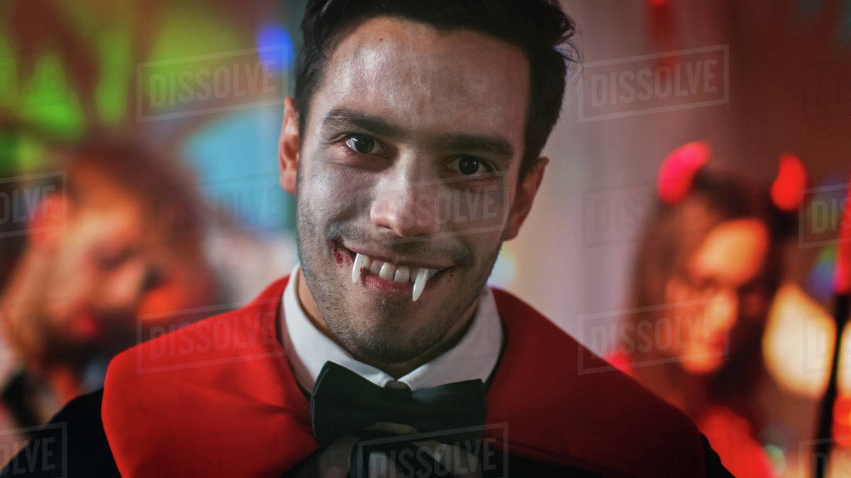 Halloween Costume Party Portrait Of Count Dracula Smiling Friendly Shows His Deadly Bloody Fangs In The Background Retro Lit Decorated Room With Scary Monsters Dancing Stock Photo Dissolve