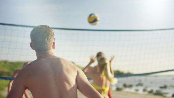 Group of young people are playing in beach volleyball on a sunny day Royalty-free stock video