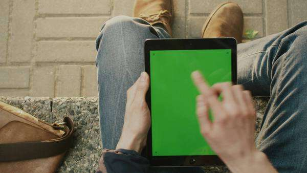 Man is using tablet on lap outdoors at sunny day. POV Royalty-free stock video