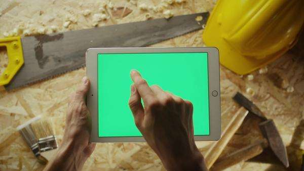 Holding tablet pc in landscape mode with workshop table with carpentry tools in the background Royalty-free stock video