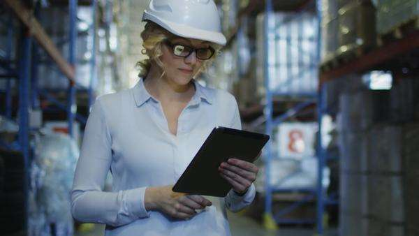 Woman manager in hard hat walking in logistic warehouse. Holding tablet in hands. Royalty-free stock video
