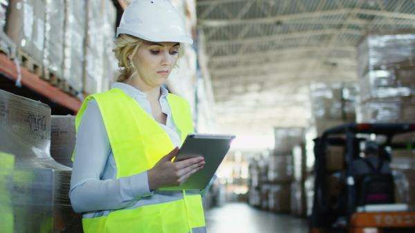 Female worker of logistic warehouse is working on tablet. Wears safety vest. Royalty-free stock video
