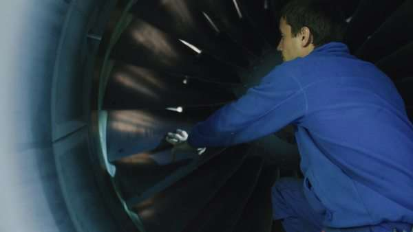 Aircraft maintenance mechanic with a flash light inspects plane turbine blades in a hangar. Royalty-free stock video