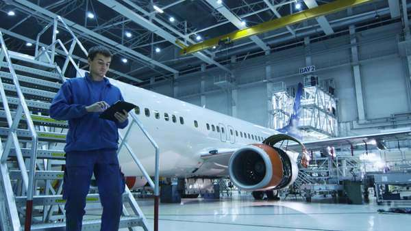 Aircraft maintenance mechanic in blue uniform is going down the stairs while using tablet in a hangar. Royalty-free stock video