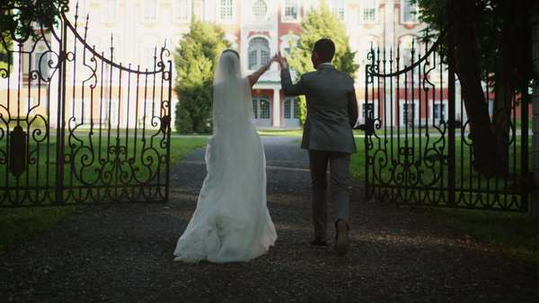 Bride and groom are moving towards a mansion in a park. Royalty-free stock video
