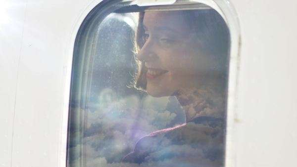Young women looks through an airplane window and smiles during flight. Royalty-free stock video