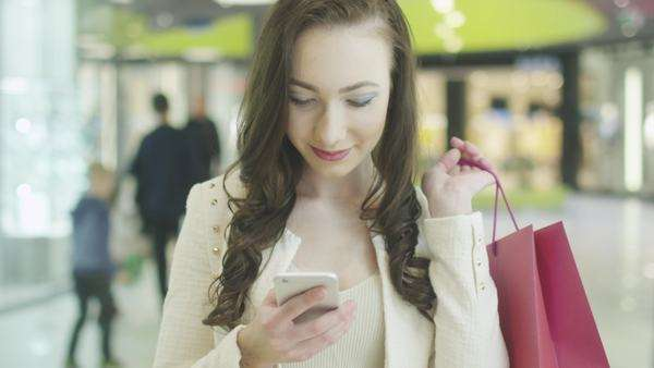 Young brunette girl with beautiful perfect smile is using mobile phone in shopping mall. Handheld shot Royalty-free stock video