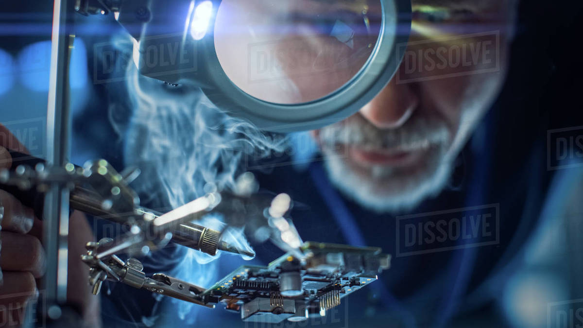 Electronics Maintenance and Repair Engineer Soldering Motherboard, Microchip and Circuit Board, Looking through Magnifying Glass, Consults Personal Computer. Close-up Low Angle Shot Royalty-free stock photo