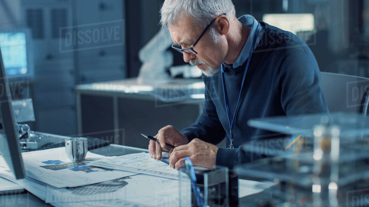 Professional Heavy Industry Engineer Draws Engine Concept Blueprint, References Computer. Engineering Bureau and Industrial Design Laboratory with Various Robotic, Architectural and Industrial Components in Sight Royalty-free stock photo