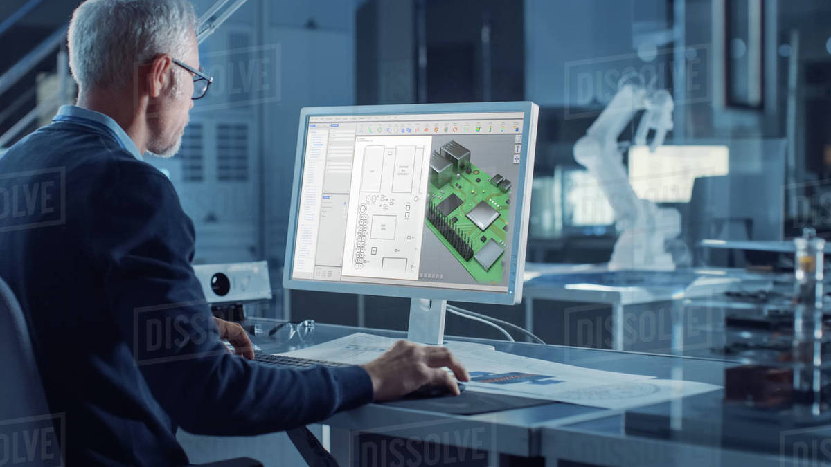 Engineer Works on Computer Uses CAD Software to Design 3D Industrial Machinery Component. In the Background Robot Arm Concept Standing in Heavy Industry Engineering Facility. Over the Shoulder Shot Royalty-free stock photo