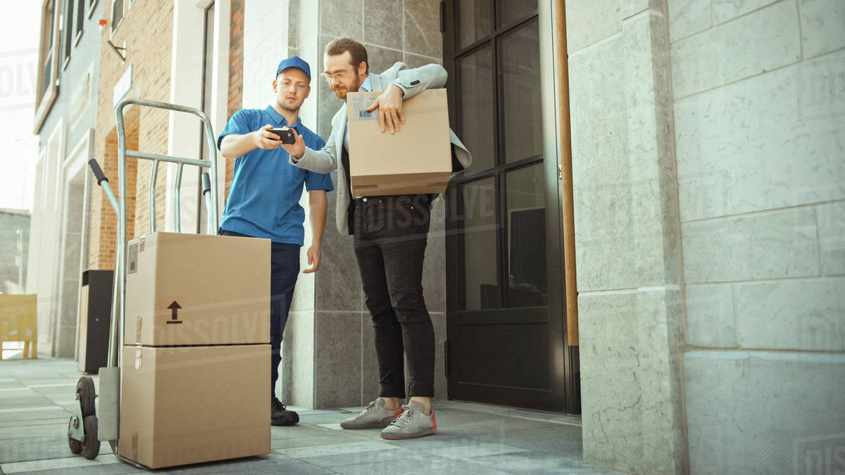 Delivery Man Pushes Hand Truck Trolley Full of Cardboard Boxes Hands Package to a Customer, Who then Signs Electronic POD Device. Courier Delivers Parcel to Man in Stylish Modern Urban Office Area Royalty-free stock photo