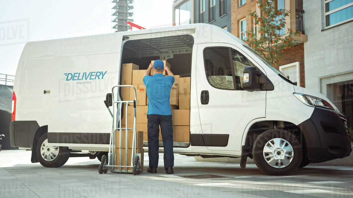 Delivery Man Uses Hand Truck Trolley Full of Cardboard Boxes and Packages, Loads Parcels into Truck / Van. Professional Courier / Loader helping you Move, Delivering Your Purchased Items Efficiently Royalty-free stock photo