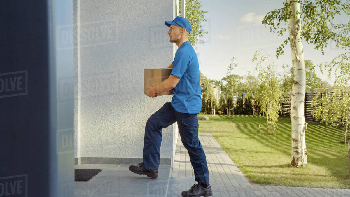 Delivery Man Holding Card Board Package Walks to the House. Delivering Postal Parcel. In the Background Beautiful Suburban Neighbourhood. Side View Royalty-free stock photo