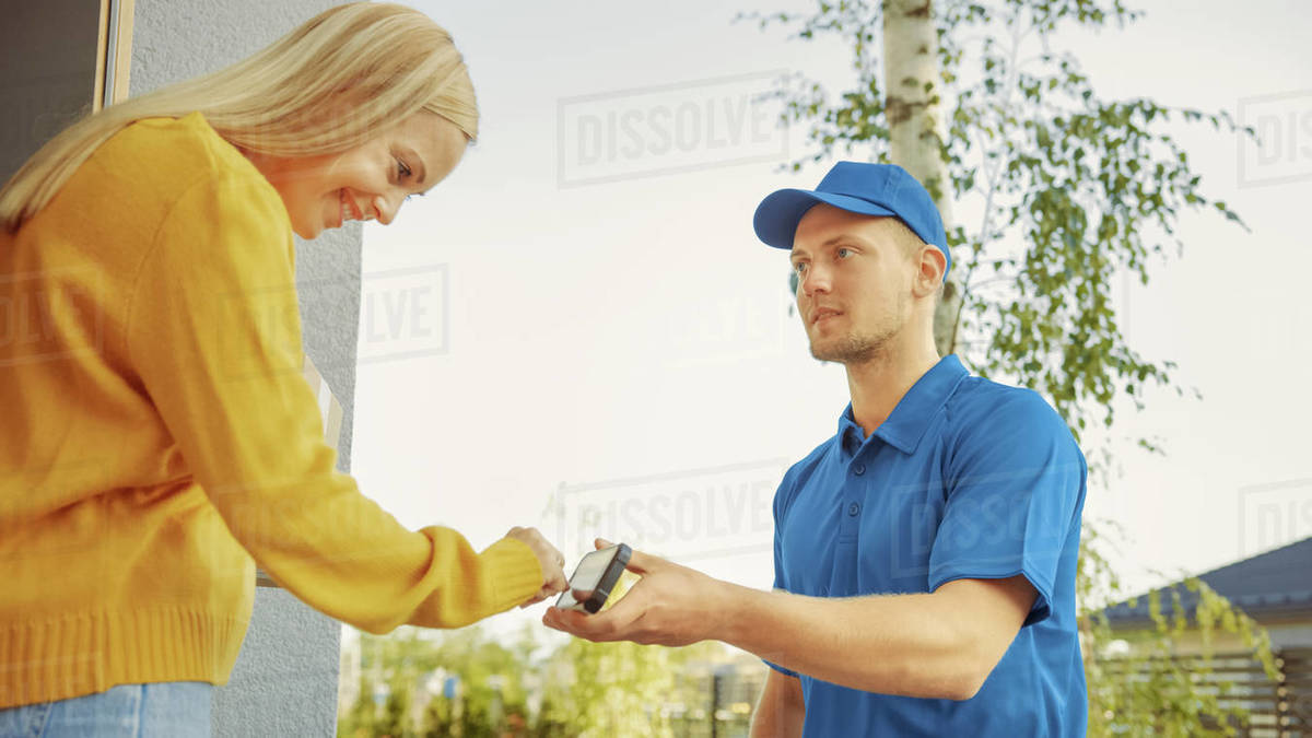 Beautiful Young Woman Meets Delivery Man who Gives Her Cardboard Box Package, She Signs Electronic Signature POD Device. Courier Delivering Parcel in the Suburban Neighborhood Royalty-free stock photo