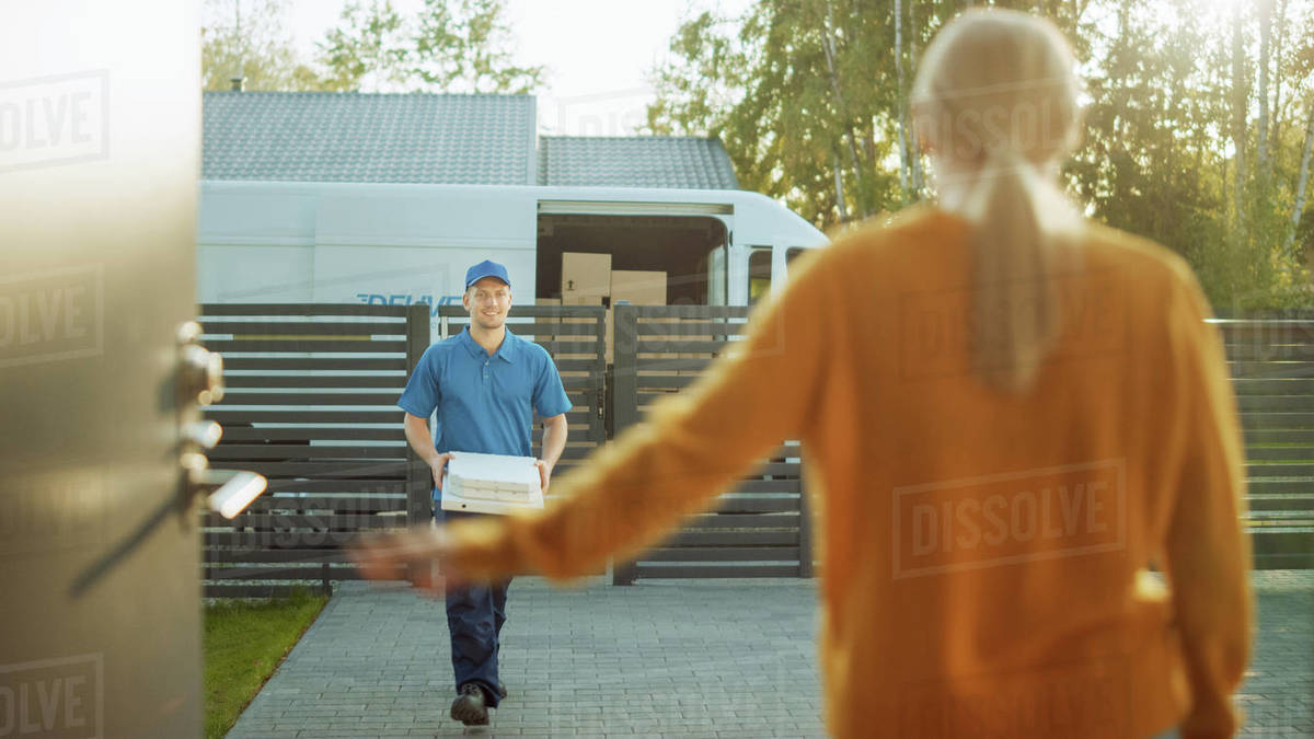 Beautiful Young Woman Opens Doors of Her House and Meets Pizza Delivery Guy who Carries Cardboard Boxes Full of Tasty Steamy Pizza. Royalty-free stock photo