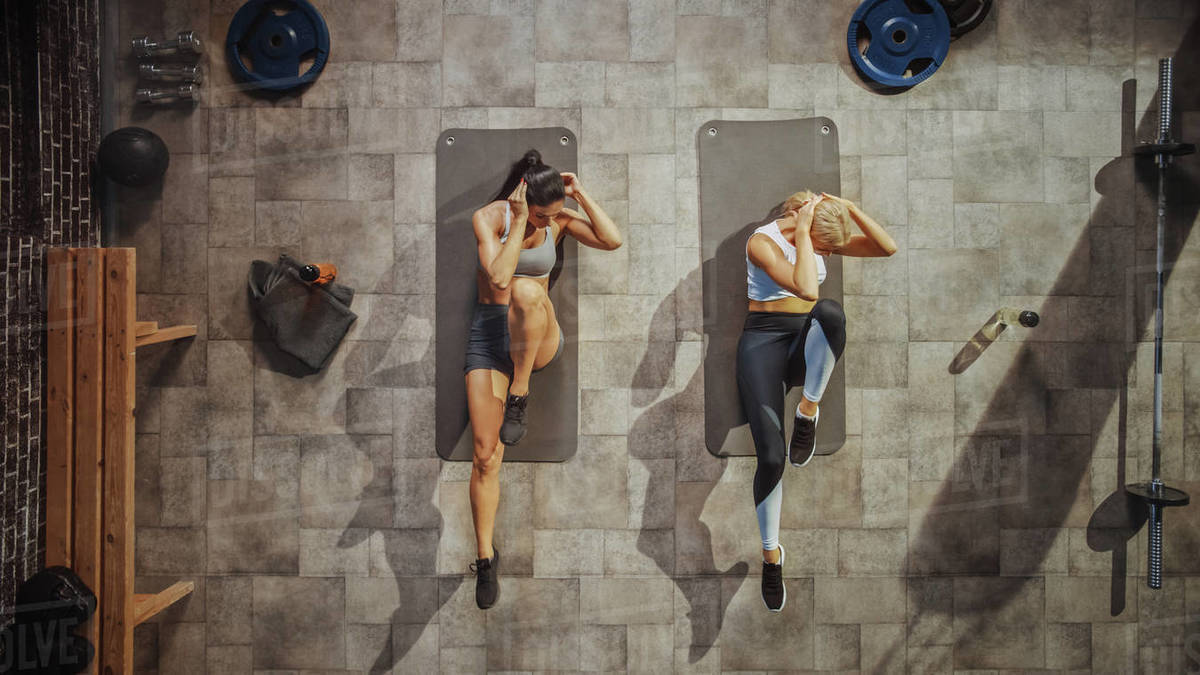 Top View Shot of Two Professional Female Bodybuilders Doing Bicycle Crunches while Lying on the Yoga Mats in Hardcore Gym. Muscular and Athletic Beautiful Girls Muscle, Power and Cardio Workout. Royalty-free stock photo