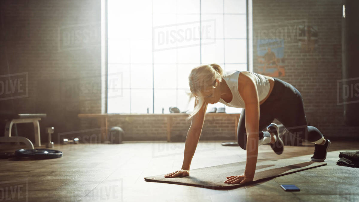 Beautiful and Young Girl Doing Running Plank Exercise on Her Fitness Mat. Athletic Woman Does Mountain Climber Workout in Stylish Hardcore Gym Royalty-free stock photo