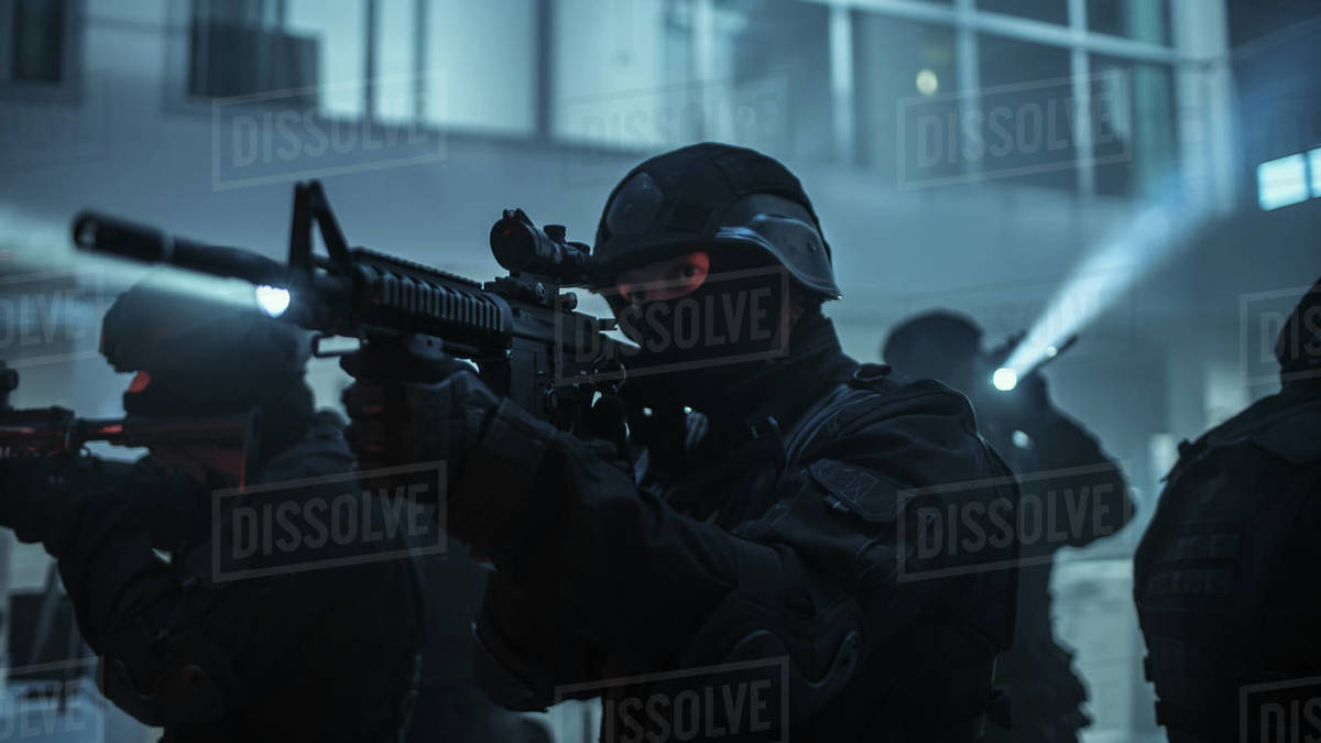 Masked Squad of Armed SWAT Police Officers Stand in Dark Seized Office Building with Desks and Computers. Soldiers with Rifles and Flashlights Surveil and Cover Surroundings. Royalty-free stock photo