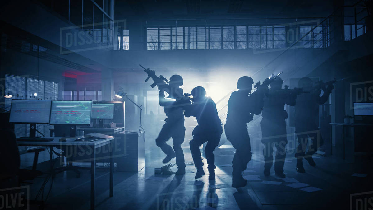Masked Squad of Armed SWAT Police Officers Storm a Dark Seized Office Building with Desks and Computers. Soldiers with Rifles and Flashlights Move Forwards and Cover Surroundings. Royalty-free stock photo