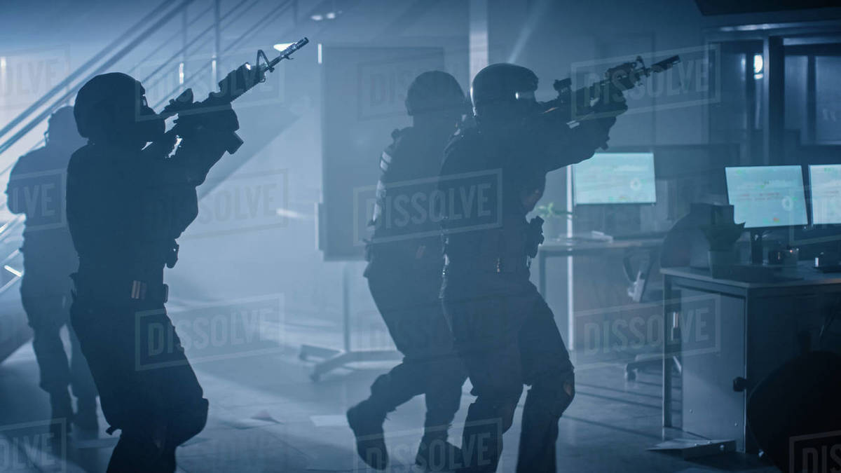 Shot of Masked Squad of Armed SWAT Police Officers Storm a Dark Seized Office Building with Desks and Computers. Soldiers with Rifles and Flashlights Move Forward and Cover Surroundings. Royalty-free stock photo