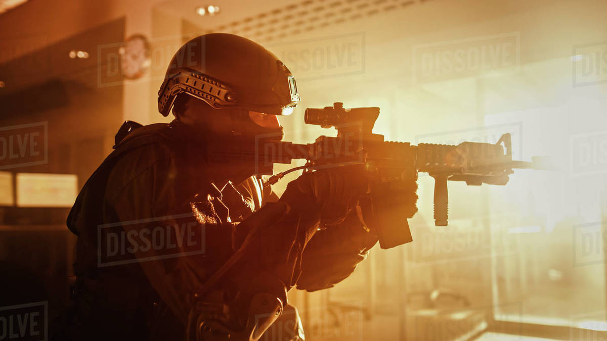Close Up Portrait of Masked Squad Member of Armed SWAT Police Officers Who Storm a Dark Seized Office Building with Desks and Computers. Soldiers with Rifles and Flashlights. Warm Color Grading. Royalty-free stock photo