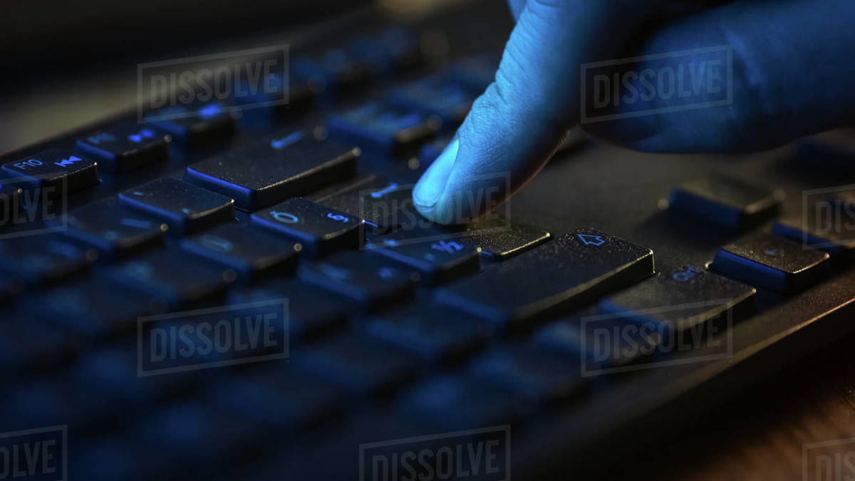 Close-up Macro Shot: Person Using Black Computer Keyboard, Pressing Enter Button Confidently. Working, Writing Emails, Using Internet. Dark and Green Colors Royalty-free stock photo