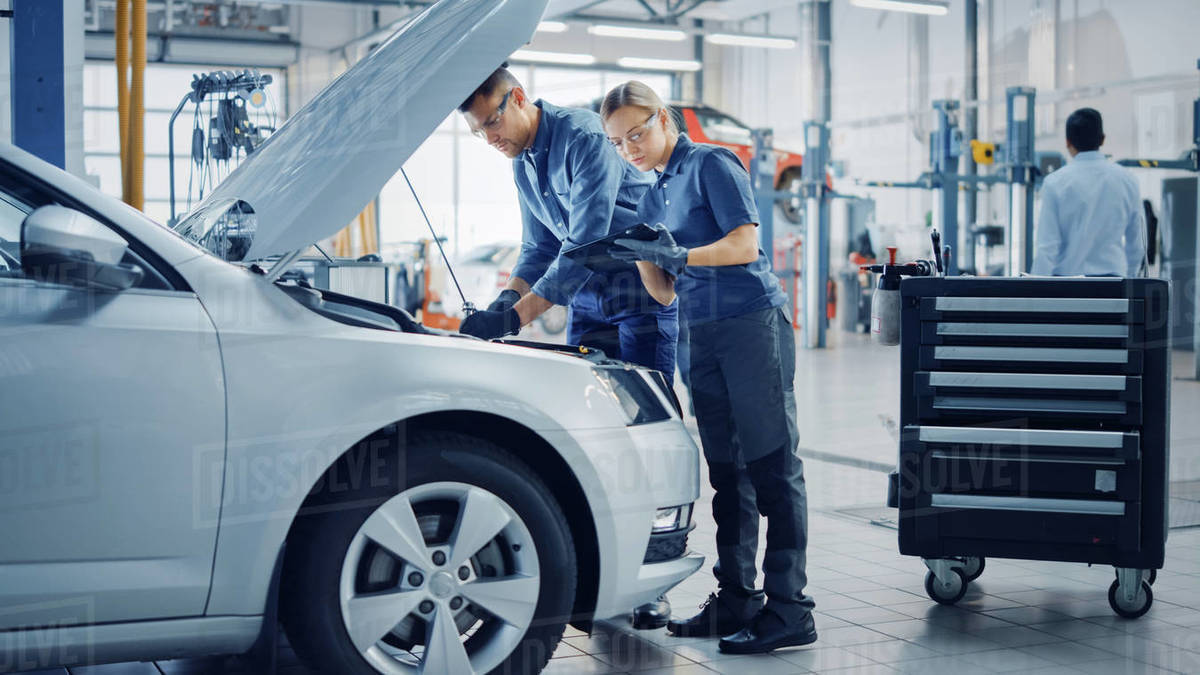 Two Mechanics in a Service are Inspecting a Car After They Got the Diagnostics Results. Female Specialist is Comparing the Data on a Tablet Computer. Repairman is Using a Ratchet to Repair the Faults. Royalty-free stock photo