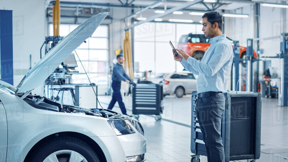Car Service Manager Uses a Tablet Computer with an Augmented Reality Diagnostics Software. Specialist Inspecting the Car in Order to Find Broken Components Inside the Engine Bay. Royalty-free stock photo