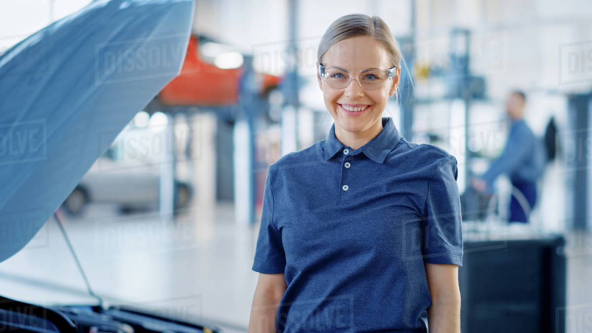 Beautiful Empowering Female Car Mechanic is in a Vehicle Service. She Looks Happy, Smiles and Looks at a Camera. Specialist is Wearing Safety Glasses. Royalty-free stock photo