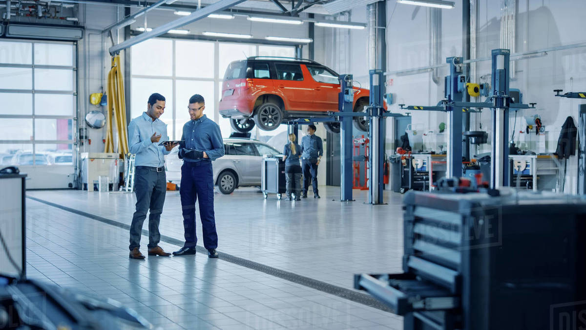 Manager Checks Diagnostics Results on a Tablet Computer and Explains a Vehicle Breakdown to a Handsome Mechanic. Car Service Employees Talk while Standing in a Garage. Modern Clean Workshop. Royalty-free stock photo