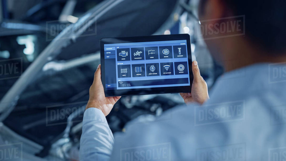 Car Service Manager or Mechanic Uses a Tablet Computer with a Futuristic Interactive Diagnostics Software. Specialist Inspecting the Vehicle in Order to Find Broken Components In the Engine Bay. Royalty-free stock photo