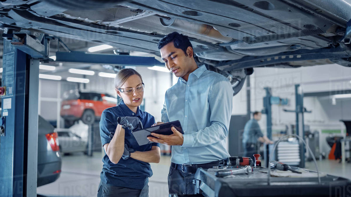 Female Mechanic Talking to a Manager Under a Vehicle in a Car Service. Specialist is Showing Info on a Tablet Computer. Empowering Woman Wearing Gloves and Safety Gloves. Modern Clean Workshop. Royalty-free stock photo