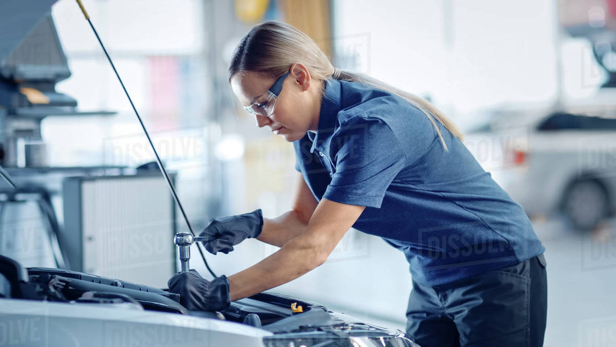 Beautiful Empowering Female Mechanic is Working on a Car in a Car Service. Woman in Safety Glasses is Fixing the Engine. She's Using a Ratchet. Modern Clean Workshop with Vehicles. Royalty-free stock photo
