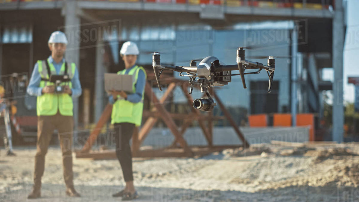 Diverse Team of Specialists Pilot Drone on Construction Site. Architectural Engineer and Safety Engineering Inspector Fly Drone on Commercial Building Construction Site Controlling Design and Quality Royalty-free stock photo
