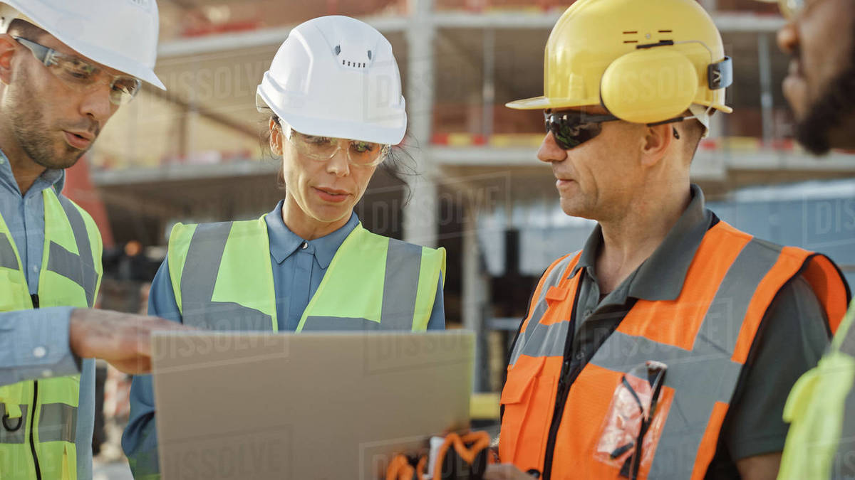 Diverse Team of Specialists Use Laptop Computer on Construction Site. Real Estate Building Project with Machinery: Civil Engineer, Investor, Businesswoman and Builder Discussing Blueprint Plan Royalty-free stock photo