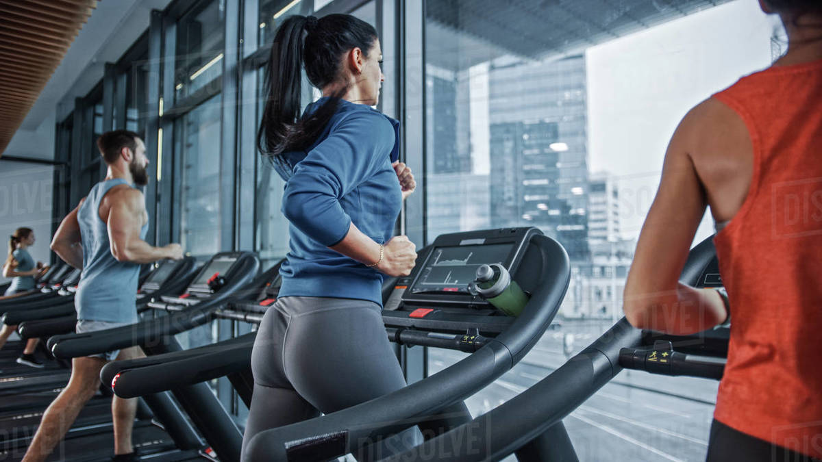 Fit Athletic Woman Running on the Treadmill, Doing Her Fitness Exercise. Muscular Women and Men Actively Training in the Modern Gym. Sports People Workout in Fitness Club. Side View Royalty-free stock photo