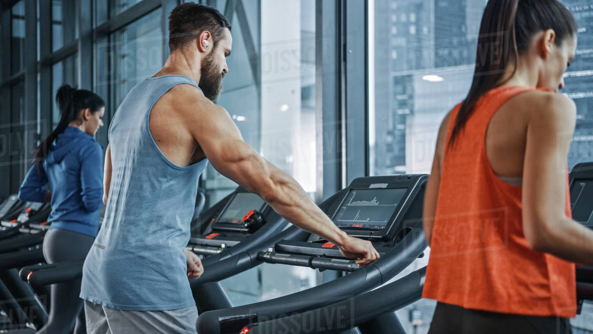 Muscular Male Athlete Uses Wireless Headphones, Plays Podcast or Training Playlist while Running on a Treadmill. Leg and Cardio Gym Day for Strong Sportsman. In Foregorund Fit Beautiful Women Running Royalty-free stock photo