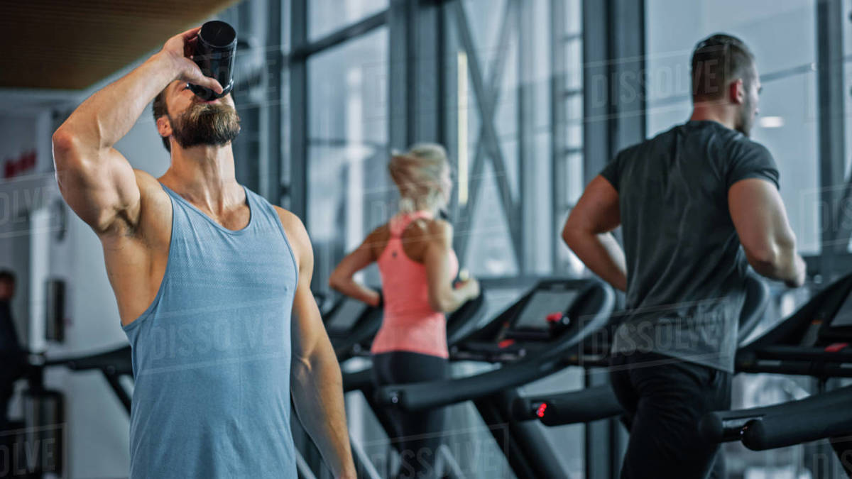 Muscular Heavyweight Champion Walks Through Gym, Drinks Protein Cocktail from Tumbler for Hydration and Muscle Mass. In the Background Sports People Running on Treadmills Royalty-free stock photo