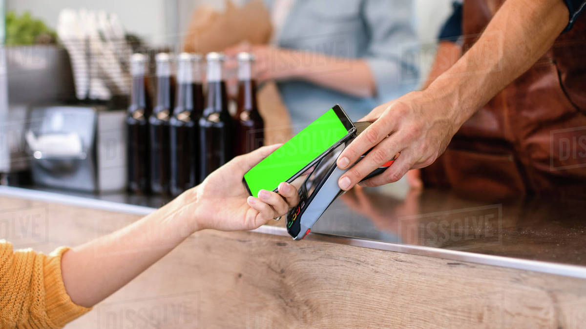 Young Woman is Using Her Smartphone with Green Screen for Contactless Payment. She is Paying for Gourmet Street Food. Eco Friendly Gluten Free Food Court Selling Modern Fusion Cuisine Royalty-free stock photo