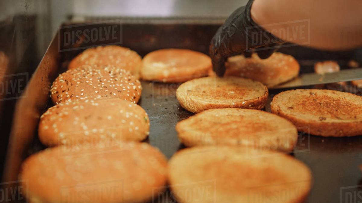 Tasty Shot of a Cook Flipping Burger Buns with Sesame Seeds on a Hot Gas or Electric Griller. Fresh Gourmet Burgers are Being Prepared. Royalty-free stock photo