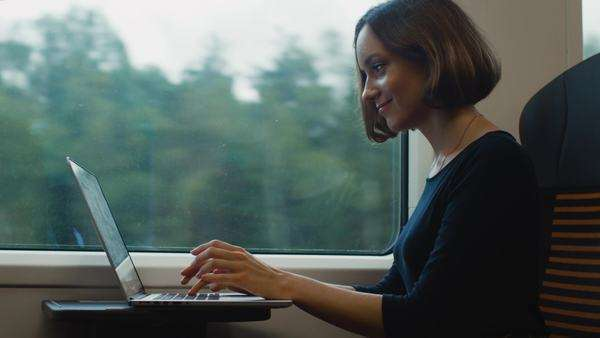 Woman working on laptop early in the morning in moving train. Royalty-free stock video