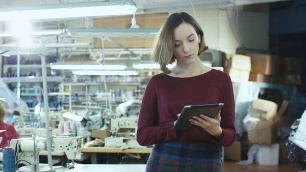 Young female with a tablet is walking through a clothing workshop and meeting employees. Royalty-free stock video